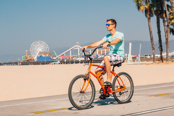 Chilling on a bike down the Venice beach in LA. Young man riding a bike by the beach. Santa Monica amusement park in the background.