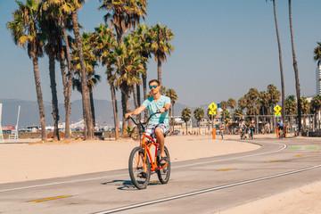 Man riding a beach bike near Venice beach in Los Angeles by the Santa Monica pier.