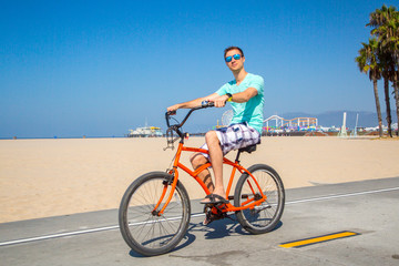 Young man riding a beach bike down the Venice beach in Los Angeles near Santa Monica pier.