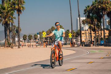 Young man riding a beach bike down the Venice beach in Los Angeles near Santa Monica pier.