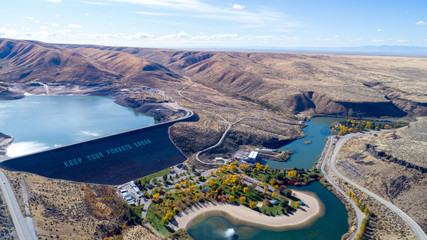 Idaho Dam in the desert with autumn trees in a park at the base
