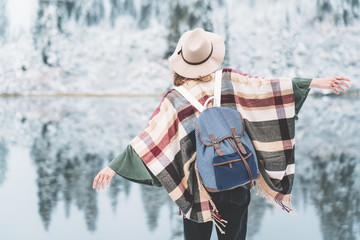 Young woman enjoying incredible nature landscape. Wearing hat, poncho and backpack. Winter is coming, first snowfall. Wanderlust and boho style