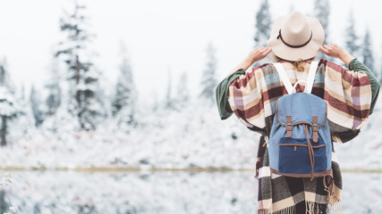 Traveling woman looking and enjoying incredible nature landscape. Wearing hat, poncho and backpack. Winter is coming, first snowfall. Wanderlust and boho style