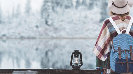 Traveling woman sitting with oil lamp in front of amazing frozen landscape. Wearing hat, poncho and backpack. Winter is coming, first snowfall. Wanderlust and boho style
