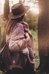 stylish hipster traveler girl in hat with backpack exploring in woods in amazing evening sunshine light. woman looking in sunlight. space for text. atmospheric moment. wanderlust