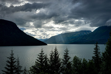 God rays with clouds and trees in foreground in Alaska United St