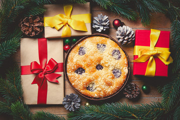 Christmas pie and gift boxes around on wooden table