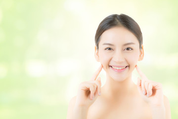 Portrait of beautiful asian woman makeup of cosmetic - girl hand touch cheek and smile on attractive face with skin healthcare concept on nature green background.