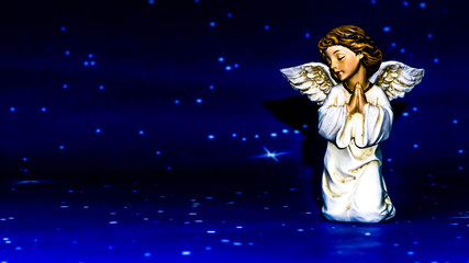 Praying angel on a starry background.
