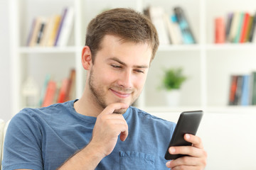 Man dating on line with a smart phone at home