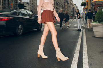 Sexy female with long legs wearing mini skirt and shoes crossing city street