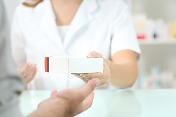 Pharmacist giving a medicament to a customer