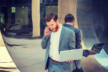 American Businessman with beard, mustache working in New York, wearing cadet blue suit, standing against metal mirror wall, working on laptop computer, talking on cell phone. Instagram filtered effect