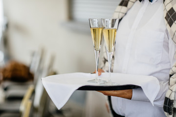 Waitress holding a dish of champagne and wine glasses at some festive event, party or wedding reception