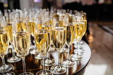 Elegant glasses with champagne standing in a row on serving table during party or celebration