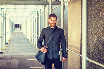 American student with beard, mustache traveling in New York, wearing black shirt, shoulder carrying leather bag, holding laptop computer, walking on sidewalk bridge. Instagram filtered effect..