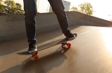 skateboarder legs skateboarding on skatepark ramp