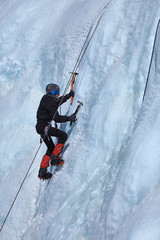 An ice climber makes his way on a frozen waterfall.