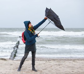 a woman tries to hold an umbrella in a storm