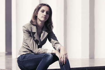 Young fashion woman in grey blazer sitting on the steps