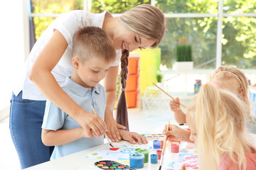 Little boy with teacher at painting lesson in classroom