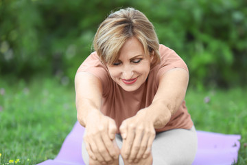 Beautiful mature woman practicing yoga in park