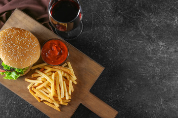 Wooden board with yummy french fries on table