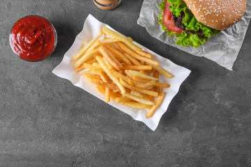 Paper container with yummy french fries on table