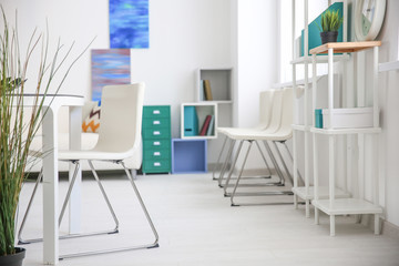 Modern room interior with white chairs and shelving unit