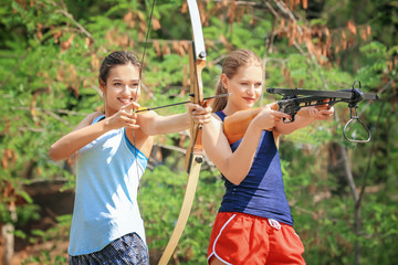Young women shooting bow and crossbow outdoors
