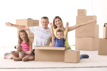 Happy family unpacking cardboard boxes in room at new house