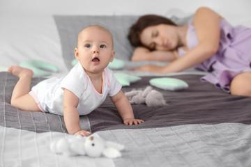 Cute awaken baby near sleeping mother at home
