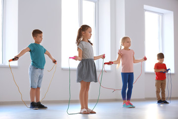 Adorable children skipping rope indoors