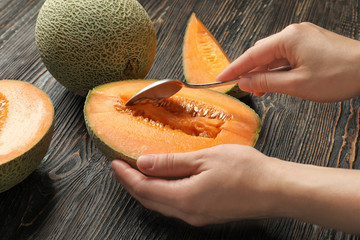 Woman taking seeds out of melon on wooden table