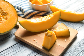Cutting board with sliced melon on wooden background