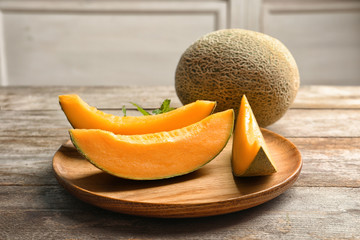 Wooden plate with sliced melon on kitchen table