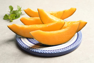 Plate with sliced melon on grey background
