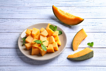 Plate with sliced melon on wooden background