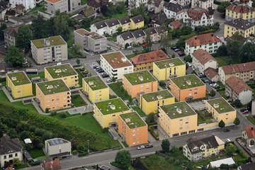 Luftaufnahme von in Gelbtönen angemalten vierstöckigen Mehrfamilienhäusern mit begrünten Dächern in der Schweiz