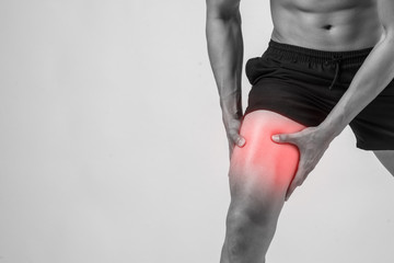 Young sport man with strong athletic legs holding knee with his hands in pain after suffering ligament injury  isolated on white.