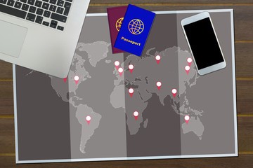 World map and pins with laptop, passport and smart phone on a wooden background