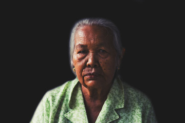 Portrait of  depress and hopeless elderly woman isolated on black