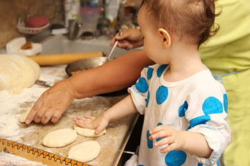 woman baking pies in kitchen with little one-two granddaughter. Grandma cooks pies and learn child. making pie by hand. Transfer of experience from grandmother to grandson. Preservation of traditions