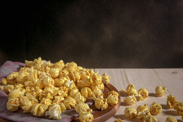Caramel covered popcorn on wooden table, mystic photography and selective focus