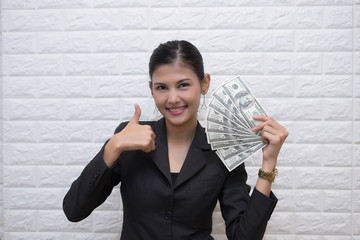 Happy young business woman holding money