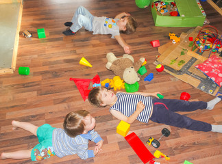 Children lie on the floor among the toys. The children made the mess and lay down on the floor..