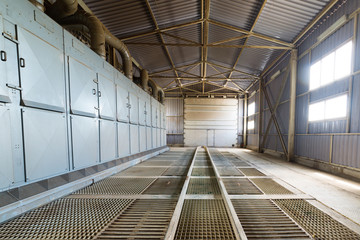 A large hangar with a floor made of steel gratings.
