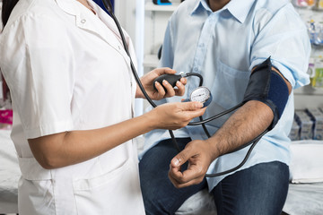 Doctor Holding Dial While Measuring Man's Blood Pressure
