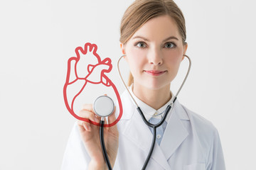 young female doctor and heart shape. Medical checkup concept.