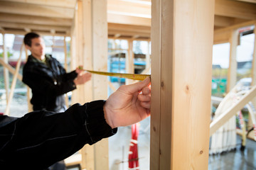 Cropped Image Of Carpenter Measuring Wood With Help Of Colleague